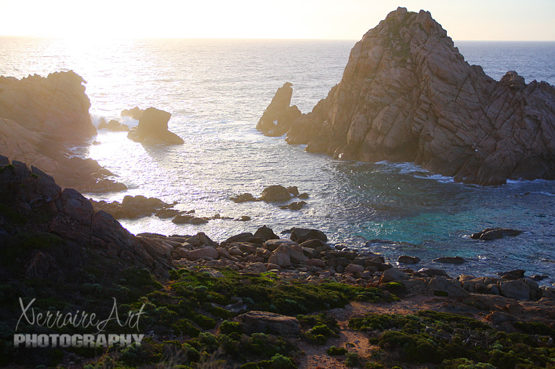 And here it is the rock they call Sugarloaf, surrounded by amazing turquoise waters, rocks, sea foam, and a bright setting sun with sea spray.