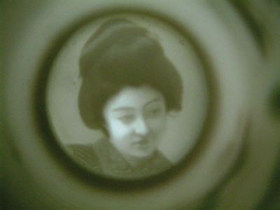 geisha at bottom of tea cup